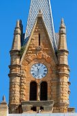 Old sandstone church tower with large clock, South Africa