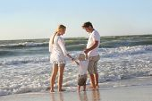 stock photo of children walking  - A happy family of three people including mother father and young child are holding hands and walking along the ocean shore on a white sand beach during a summer vacation - JPG