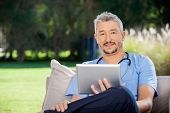 Portrait of male caretaker holding tablet computer while sitting at nursing home porch