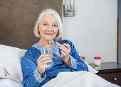 Portrait of smiling senior woman taking medicine on bed at nursing home