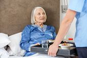 stock photo of male nurses  - Midsection of male nurse serving breakfast to senior woman on bed in nursing home - JPG