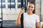 Portrait of smiling female athlete standing at gym