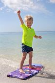 Happy Child Standing On Boogie Board In Ocean