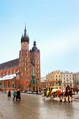 Horse Carriage In Front Of Mariacki Church On Main Square Of Krakow