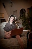 Beautiful young woman sitting on sofa working on laptop, in boudoir scenery. Attractive brunette