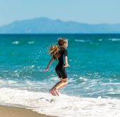 Happy cute little girl jumping in a wetsuit on the beach