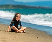 cute little girl sitting in a wetsuit on the beach