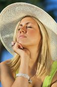 A beautiful young blond woman wearing a sun hat eyes closed enjoyed getting a sun tan on her face