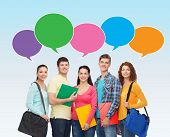 school, education, communication and people concept - group of smiling students with folders and school bags over blue background with text bubbles
