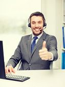 business, communication and technology concept - friendly male helpline operator with headphones and computer at call center showing thumbs up