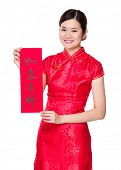 Woman with traditional cheongsam and holding Fai Chun, phrase meaning is everything goes smooth and good luck