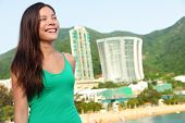 Hong Kong tourist woman at Repulse Bay beach. Beautiful Asian woman in summer dress enjoying view. Hong Kong lifestyle image.