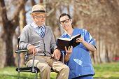 Male nurse reading a book to a senior man in a wheelchair in park
