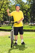 Full length portrait of a middle aged man in sportswear giving thumb up next to his bike in a park