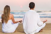 Man And Woman Meditating In Front Of Sea