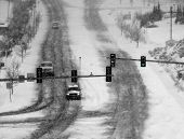 Snowy winter road with cars driving on roadway in snow storm and traffic lights