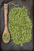 High angle shot of a pile of green split peas and a wooden spoon on a well used metal baking sheet. Vertical Format.