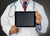 Closeup of a doctor holding a tablet computer with a blank Chalkboard screen in front of his torso.  Horizontal format over a light to dark gray background. Man is unrecognizable.