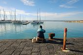 SIRACUSA, ITALY - JENUARY 03: rear view of man sitting and fishing on the Ortigia pier, Old Town of Siracusa. Sicily. Shot in 2015