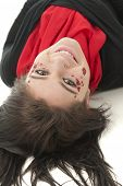 A beautiful teen looking back at the viewer as she lays on her back.  She's wearing red and black and her face is decorated in sparkly hearts, rhinestones and a pair of lips.  On a white background.