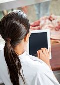 High angle rear view of female butcher using digital tablet in store