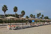 Tourists Lying On The Loungers Private Beach In Mediterranean Resort.