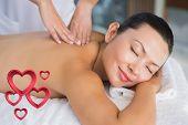 Content brunette getting a back massage against pink hearts