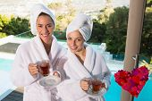 Smiling women in bathrobes having tea against heart