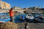 SIRACUSA, ITALY - JAN 03: fishing boats and fisherman in the darsena of Ortigia, Old Town of Siracusa in Sicily. The fisherman in foreground checks and arranges a fishing net. Shot in 2015