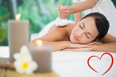 Beautiful brunette enjoying a herbal compress massage against heart