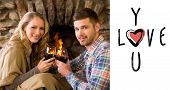 Romantic couple toasting wineglasses in front of lit fireplace against cute valentines message