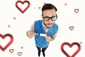 Geeky hipster looking at camera pointing at card against hearts