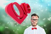 Geeky hipster with kisses on his face against digitally generated dandelion seeds on green background