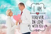 Older affectionate couple holding pink heart shape against digitally generated pink and blue girly design