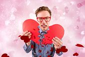 Geeky hipster holding a broken heart against valentines heart design