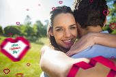 Loving and happy woman embracing man at park against happy valentines day