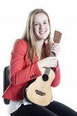 image of ukulele  - teenage girl holds ukulele in studio against white background - JPG