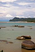 stock photo of langkawi  - Large boulders on the black sand beach in Langkawi Island - JPG