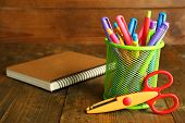 Metal holder with different pens, notebook and scissors on rustic wooden background