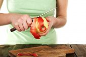 Woman hands peeled apple with knife on wooden table, isolated on white background