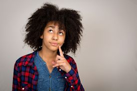 stock photo of wacky  - Young teenage girl with wacky afro hair looking up thinking and solving problems isolated against a grey background - JPG