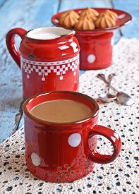 stock photo of milkman  - Drink brown red old ceramic mug against the milkman and biscuits  - JPG