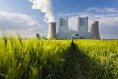 stock photo of fire-station  - Low angle view of a shiny new lignite power station behind a rye field with wheel tracks leading to it - JPG