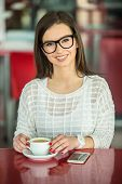 picture of pullovers  - Young beautiful smiling girl in glasses and white pullover sitting in urban cafe with a cup of coffee - JPG