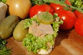 stock photo of baguette  - Slice of baguette with tuna fillet garnished with lettuce onion tomato and pickles on a wooden board - JPG
