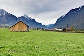 pic of snow capped mountains  - Lone wood cabin in the green Austrian countryside with snow - JPG
