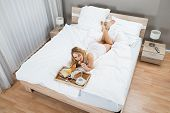pic of bed breakfast  - High Angle View Of A Woman Lying On Bed Having Breakfast - JPG