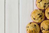 foto of chocolate muffin  - Banana Chocolate Chip Muffins from Above with Pink Polka Dot Muffin Paper on White Wooden Table with Copy Space - JPG