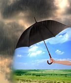 picture of rain clouds  - Black umbrella in hand protecting good weather from dark clouds of rain - JPG