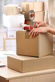 image of packing  - Woman packs parcel in post office - JPG